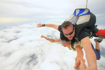 Girl above the clouds, free falling during sky dive