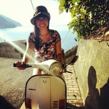 Girl on white moped vespa posing on a hill with the ocean view behind her in Italy.