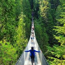Girl crossing suspension bridge surrounded by tall green trees in Vancouver, Canada