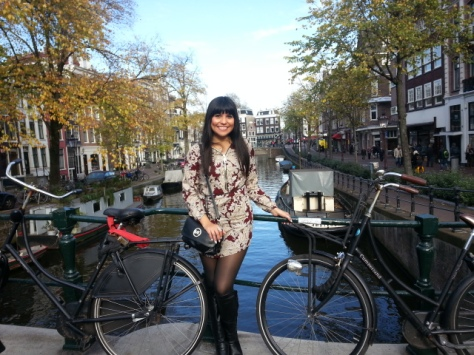 GIrl wearing black boots posing in front of bicycle in Amsterdam canal