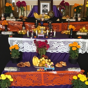 Mexican offering for the Day of The Dead with food, flowers, pictures and religious symbols.