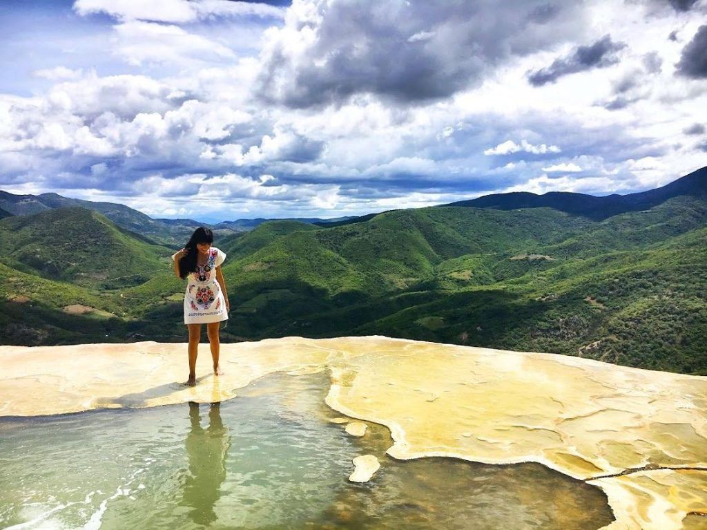 Girl standing on the edge of a cliff in a natural spring water pool and mountain range behind her in Oaxaca Mexico Hierve El Agua