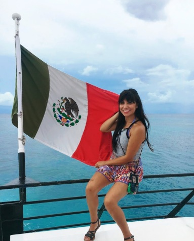 Girl on a ferry holding a Mexican flag.