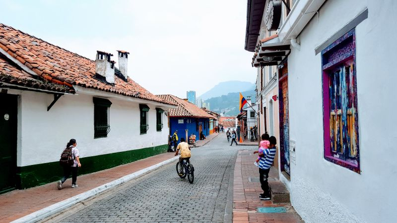 Streets in Bogota with school girl, boy riding a bike, mountain backdrop and white houses.